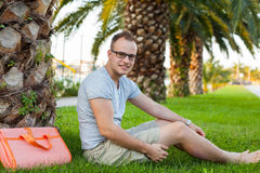 Young tourist sitting under palm tree. Positive emotion. Vacatio Stock Photo