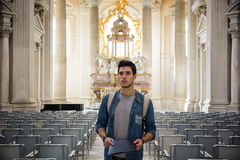 Young tourist standing in church while looking away. Young thoughtful tourist standing in church between rows of chairs while looking away Stock Image