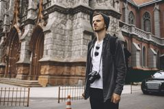 Young tourist is standing near gothic church in the middle of the road. He is looking straight forward trying to see something. Guy looks very serious Royalty Free Stock Images