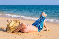 Young tourist sunbathing on beach with sea Stock Photo