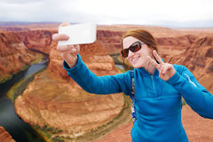 Young tourist taking a photo of herself by famous Horseshoe Bend, Arizona Royalty Free Stock Images