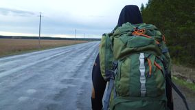 A young tourist travels with a backpack on his shoulders. A tourist hitchhiker walks along the road with a backpack on his shoulders. The weather is cloudy and stock video footage