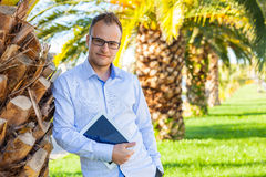 Young tourist under palm tree with mobile tablet pc. Positive em Royalty Free Stock Photography