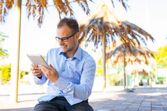 Young tourist under palm tree with mobile tablet pc. Positive em Stock Photos