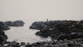 Young man walking through the rocks on the shore of the sea. Male in lopapeysa exploring the black beach alone. Young tourist walking through the rocks on the stock footage