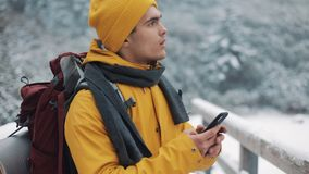 A young tourist walks on a bridge in the snowy mountains with a smartphone in his hands. Communication, social networks. Travel concept stock video