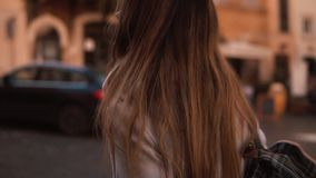 Young tourist woman with backpack walking down the street in sunny day. Pretty girl spending vacation in Europe. Thoughtful girl exploring the city stock video