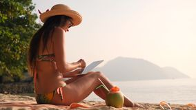 Young Tourist Woman in Bikini Using Mobile Tablet Gadget and Sitting on Tropical Paradise Sandy Beach. 4K, Slowmotion. Phuket, Thailand stock footage