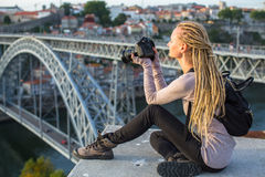 Young tourist woman with camera sitting on the viewing platform opposite the Dom Luis I bridge across the Douro river in Porto Stock Photography