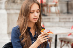 Young tourist woman eating authentic pizza outdoors. Royalty Free Stock Photos