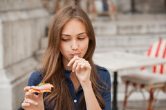 Young tourist woman eating authentic pizza outdoors. Royalty Free Stock Photo