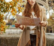 Young tourist woman on embankment in Paris, France with map. Autumn getaways in Paris. young tourist woman on embankment in Paris, France with map Stock Photos