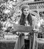Young tourist woman on embankment in Paris, France with map. Autumn getaways in Paris. young tourist woman on embankment in Paris, France with map Royalty Free Stock Photo