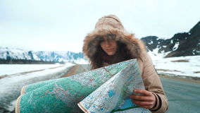 Young tourist woman exploring Mountain map while traveling in mountains in winter, vacation concept. A beautiful young tourist girl uses a paper map of the area stock video