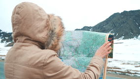 Young tourist woman exploring Mountain map while traveling in mountains in winter, vacation concept stock video footage