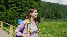 Young tourist woman goes to a picturesque place in the background of meadows, mountains and sky. Tourism and active. An attractive tourist woman goes to a stock footage