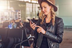 Young tourist woman in hat stands at airport, uses smartphone. Hipster girl checks email, chatting, browsing internet. Young tourist woman in hat, with backpack stock image