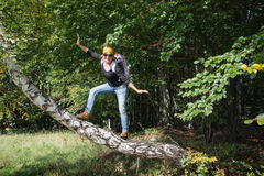 Young tourist woman is holding a balance on the birch branch Stock Photo