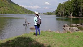 Young tourist woman looking at the beautiful mountain lake in Spanish National Park Augestortes.  stock footage