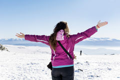Young tourist woman with open arms  in a winter  mountain Royalty Free Stock Images