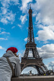 Young tourist woman with Parisian style red hat looking at Eiffel tower from the Seine river side. France Stock Photo