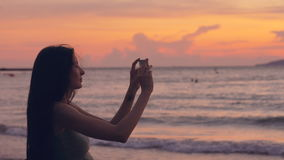 Young tourist woman photographs ocean view with smartphone during sunset at beach stock video
