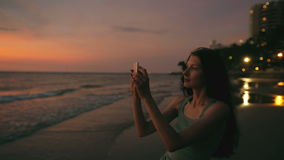 Young tourist woman photographs ocean view with smartphone during sunset at beach stock video footage