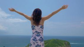 Young tourist woman put her hands up at viewpoint of beautiful sea bay landscape. Young tourist woman put her hands up at viewpoint and looking at a beautiful stock footage