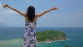 Young tourist woman put her hands up at viewpoint of beautiful sea bay landscape. Young tourist woman put her hands up at viewpoint and looking at a beautiful stock video