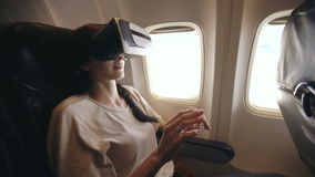 Young tourist woman relax and using VR headset for smartphone during flight in airplane stock footage