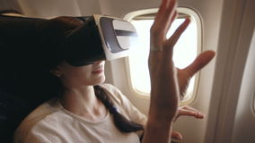 Young tourist woman relax and using VR headset for smartphone during flight in airplane stock video footage
