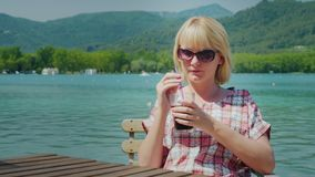 Young tourist woman relaxing in a beautiful location by the lake and mountains in Spain. Drinks Coke from a glass with a stock footage
