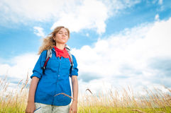 Young tourist woman relaxing in summer field. Stock Photos
