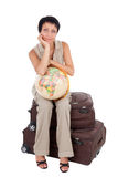 Young tourist woman sits on brown suitcase Royalty Free Stock Images