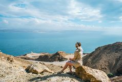 Young tourist woman is sitting on the top of the mounting and looking at a beautiful sea bay landscape stock photos