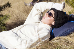 Young tourist woman sleeping on a meadow in the mountain royalty free stock image
