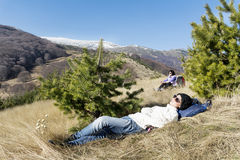 Young tourist woman sleeping on a meadow in the mountain royalty free stock photos
