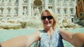 A young tourist woman takes a video with herself on the background of the famous Trevi Fountain in Rome, Italy. 4K video stock footage