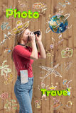 Young tourist woman is taking a picture in front of the wooden wall with trip symbolics. Stock Photo