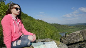 Young tourist woman travels with compass and map in the mountains. Natural green background Royalty Free Stock Photos