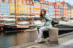 Young tourist woman visiting Scandinavia. Happy young tourist woman with backpack at Copenhagen, Nyhavn, Denmark. Visiting Scandinavia, famous European Royalty Free Stock Images