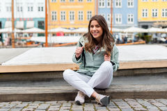 Young tourist woman visiting Scandinavia. Happy young tourist woman with backpack at Copenhagen, Nyhavn, Denmark. Visiting Scandinavia, famous European Royalty Free Stock Image