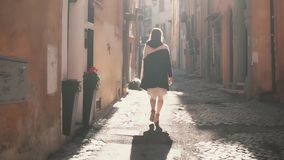 Young tourist woman walking up the small street in sunny day. Girl spending vacation in Europe, exploring old town. Young tourist woman walking up the small stock video footage