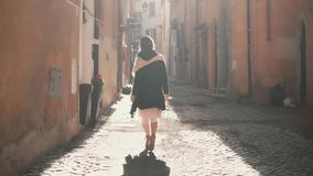 Young tourist woman walking up the street in sunny day. Pretty girl spending vacation in Europe, exploring the old city. Female spending time outside stock video footage