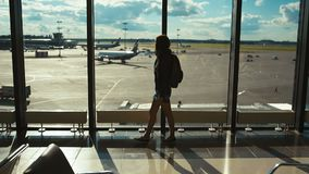 Woman tourist on the background of the airport runway stock footage