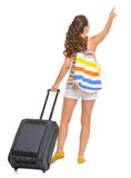 Tourist woman with bag pointing on copy space Stock Images