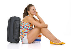 Young tourist woman with wheel bag sitting on floor Stock Photo