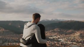 Young touristic couple enjoying mountains view.Loving couple look on each other. Young touristic couple enjoying mountains view. Tourist traveler on background stock video footage