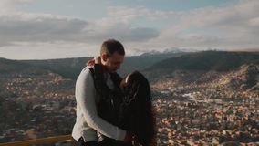 Young touristic couple enjoying mountains view.Loving couple look on each other. Young touristic couple enjoying mountains view. Tourist traveler on background stock video