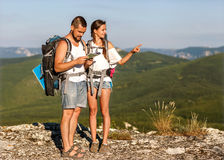 Young tourists with backpacks taking photo of a valley from top Royalty Free Stock Photography